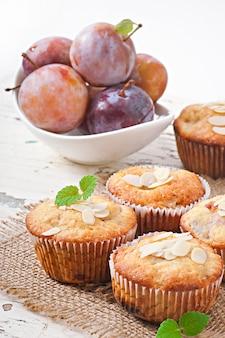 Muffins mit pflaumen und mandelblättern, verziert mit minzblättern
