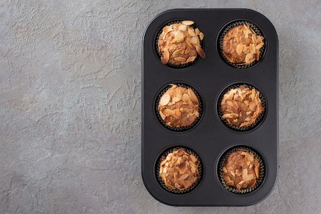 Muffins mit quark verziert mit mandelblättchen in einer auflaufform.