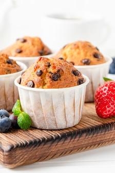 Muffins mit schokoladenstückchen auf einem holzbrett auf weißem hintergrund mit frischen beeren. platz kopieren.