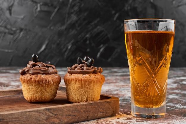 Muffins und cocktail auf einem holzbrett.