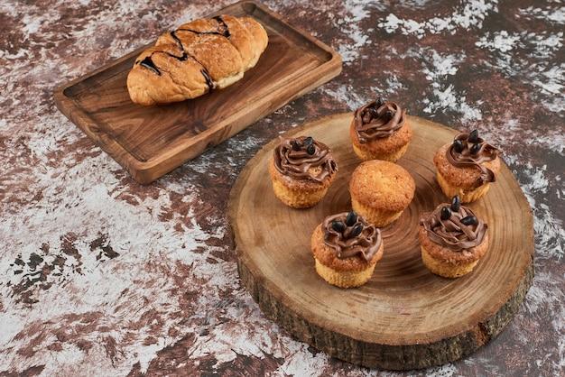 Muffins und croissant auf einem holzbrett.