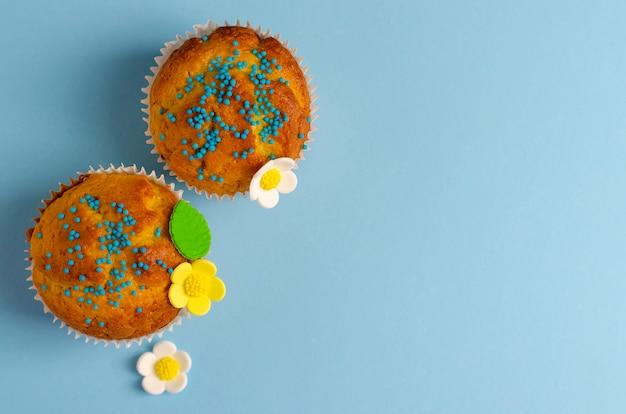 Muffins verziert mit blumen des mastixes auf blauem pastellhintergrund.