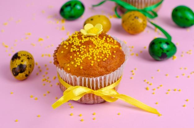 Muffins verziert mit streuseln, blüten von mastix-, grünen und gelben ostern-wachteleiern