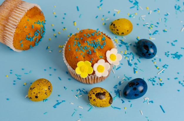 Muffins verziert mit streuseln, blüten von mastix und gelben und blauen wachtelostereiern
