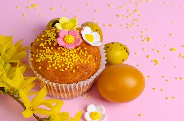 Muffins verziert mit streuseln, blüten von mastix und gelben wachtelostereiern