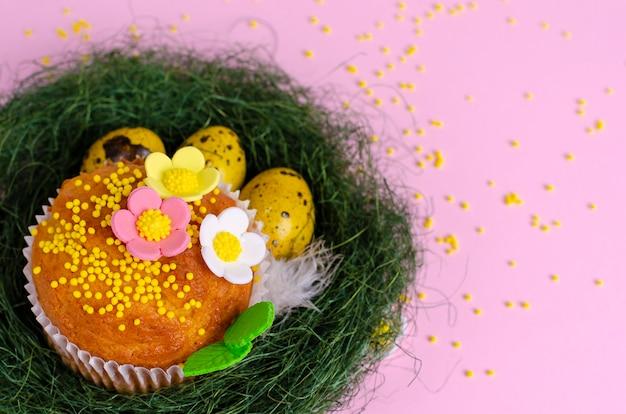 Muffins verziert mit streuseln, blumen des mastix und gelben ostern-wachteleiern im grünen nest