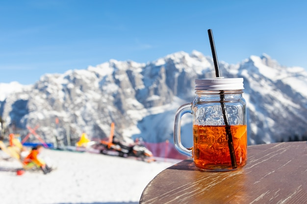 Mug aperol steht auf dem tisch des straßencafés am hang des skigebiets.
