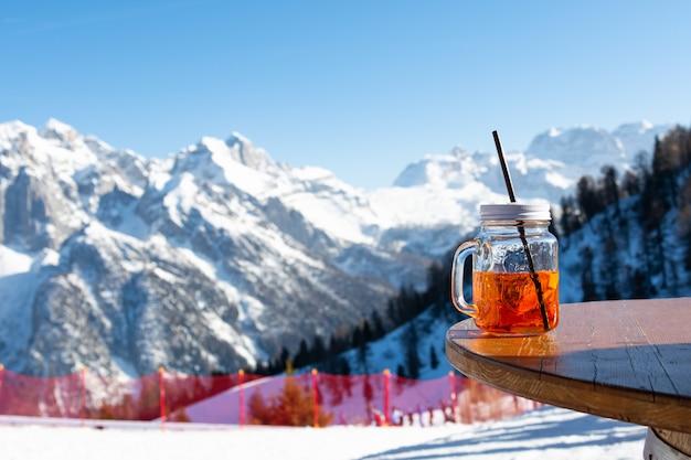 Mug aperol steht auf dem tisch eines straßencafés vor dem hintergrund der berge.