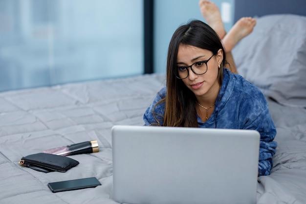 Mujer joven latina trabajando en la recamara de su casa con un ordenador portatil usando ropa comoda