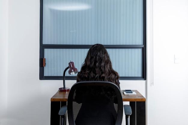 Mujer latina joven trabajando desde casa en un escritorio de madera vista desde la espalda
