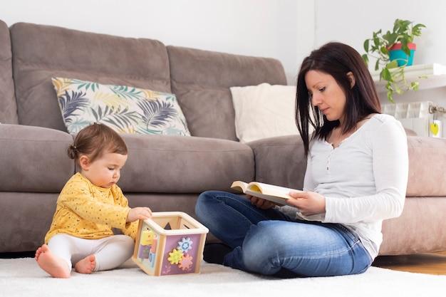 Mujer leyendo un libro junto a su hija mientras juega en el salón de casa con un cubo de madera