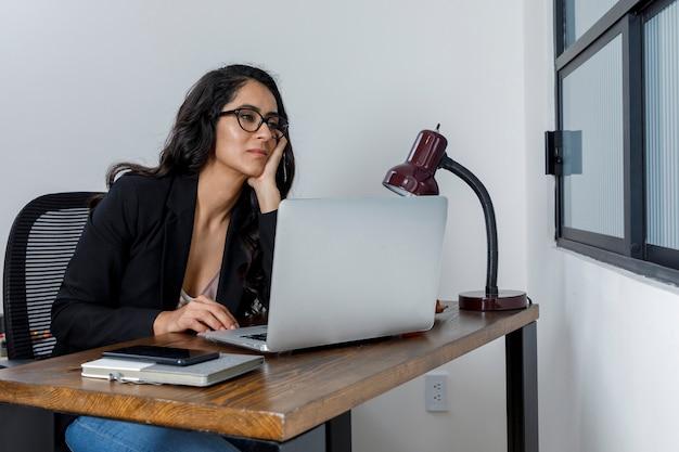 Mujer mirando por la ventana estresada de tanto trabajar en casa por la cuarentena