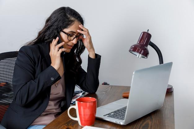 Mujer molesta hablando por telefono mientras trabaja desde cas debido a la pandemia