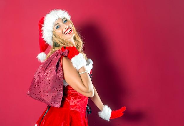 Mujer vestida con traje de navidad de santa claus sonriendo y llevando sobre su hombro un saco de r