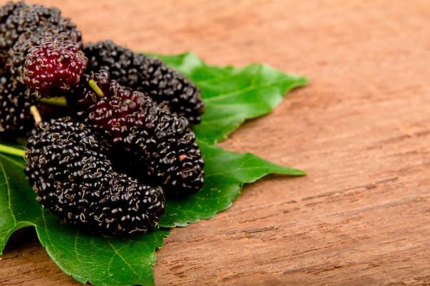 Mulberry und blatt auf altem holz