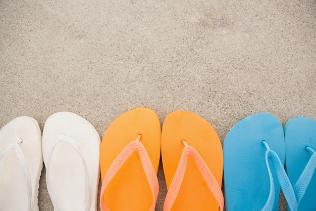 Multi-color-flip-flops in einer reihe in sand angeordnet