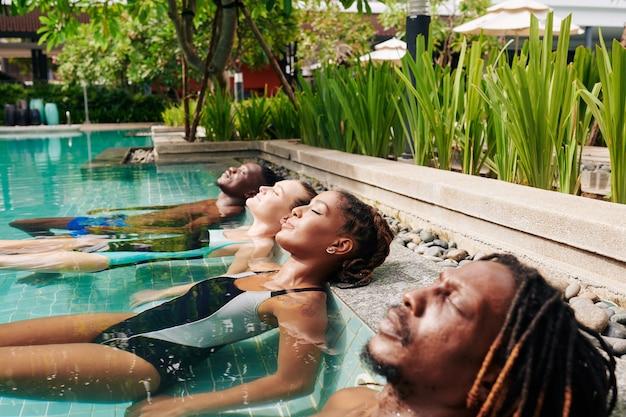 Multi-ehnische gruppe von jungen menschen, die im simming-pool mit geschlossenen augen liegen und erfrischendes wasser genießen