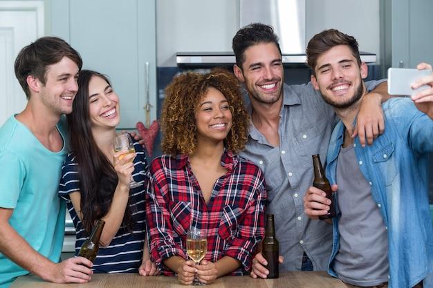 Multi ethnische freunde mit dem alkohol, der selfie in der küche nimmt