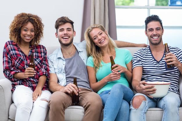 Multi ethnische junge freunde, die bier auf sofa genießen