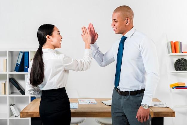 Multi ethnischer junger geschäftsmann und geschäftsfrau, die miteinander hoch fünf am arbeitsplatz gibt