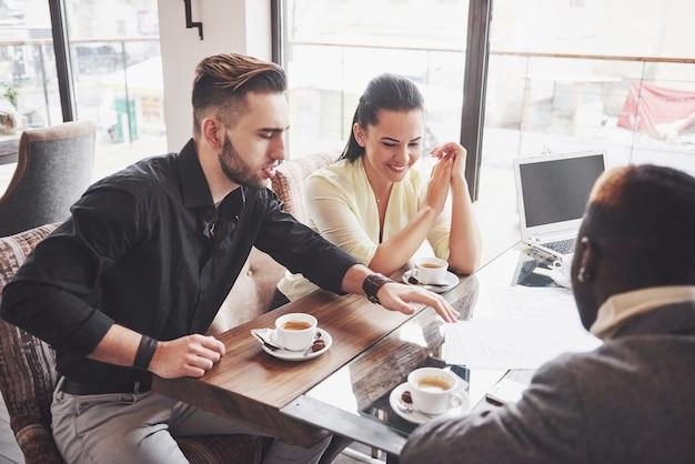Multi ethnischer leuteunternehmer, kleinbetriebkonzept. frau, die mitarbeitern etwas auf laptop-computer zeigt, wie sie um einen konferenztisch sich versammeln