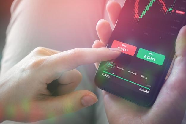 Multi-exposure-finanzdiagramme und hand mit handy. kaufen und verkaufen, handeln. hintergrundfoto des forex- und investmentgeschäftskonzepts