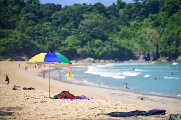 Multi farbenregenschirm auf dem strandsommergrund