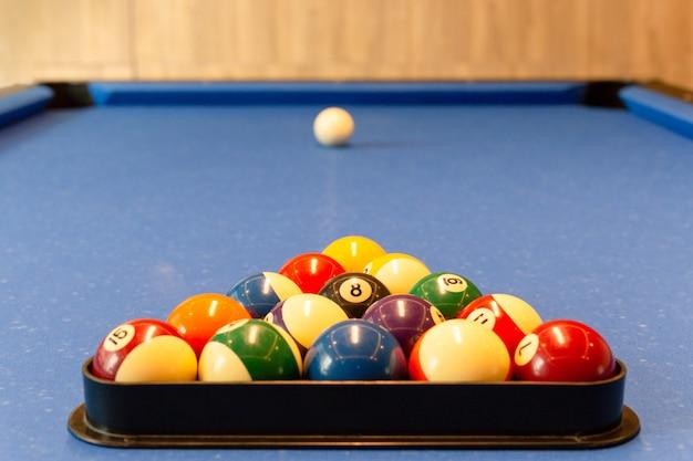 Multi farbige billardkugeln mit zahlen liegen in einer dreieckspyramide auf dem blauen tuch der tabelle.