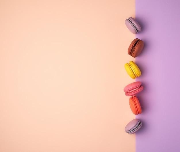 Multi farbige macarons mit sahne auf einem purpurroten beige hintergrund, flache lage
