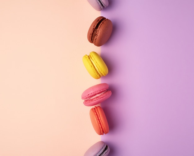 Multi farbige macarons mit sahne auf einem purpurroten beige hintergrund
