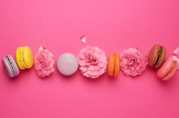 Multi farbige macarons mit sahne und ein rosa rosenknospenhintergrund