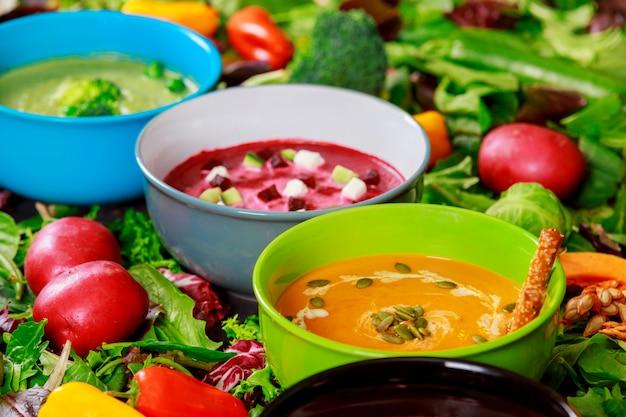 Multi farbige suppen der zusammenstellung der gemüsesahnesuppe auf bestandteilen für suppenhintergrund