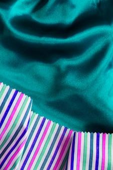 Multi farbiges gewebematerial auf seidigem grünem textilhintergrund