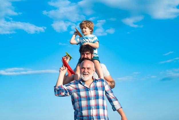 Multi-generationen-wochenend-familienspiel männer in verschiedenen altersstufen glückliches kind, das mit spielzeugpapier-flugzeug spielt ...