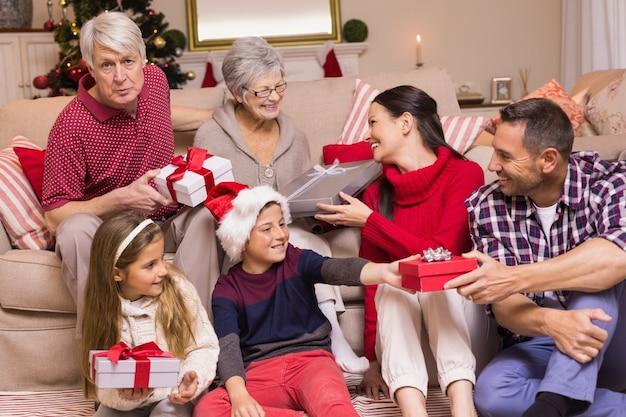 Multi generationsfamilie, die geschenke auf couch austauscht