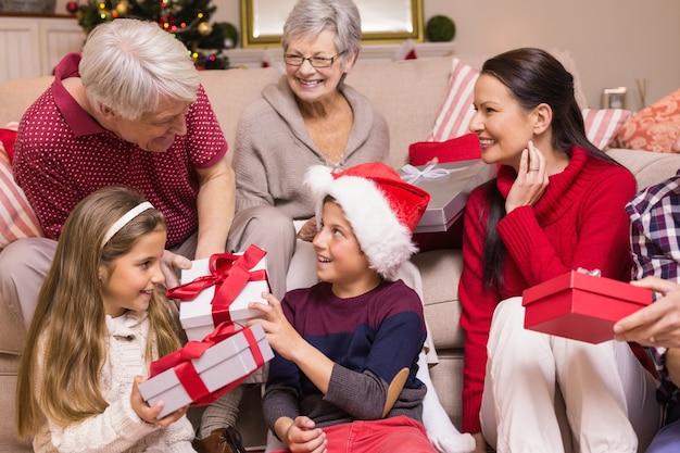 Multi generationsfamilie, die geschenke auf sofa austauscht