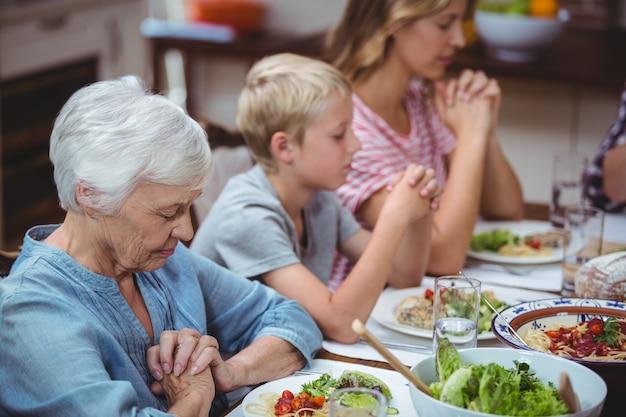 Multi generationsfamilie, die mit der oma sitzt an speisetische betet