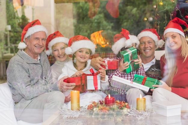 Multi generationsfamilie, die viele geschenke auf sofa hält