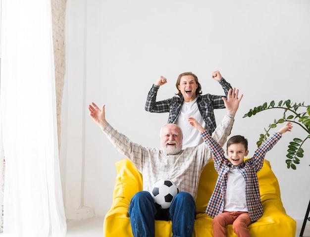 Multi generationsmänner, die fußball im freuenden gewinn des fernsehens aufpassen