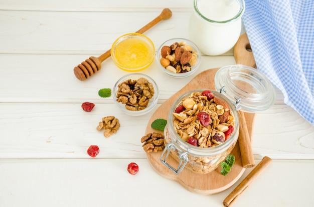 Multicereal hausgemachtes bio-müsli mit einer mischung aus nüssen, getrockneten kirschen, honig, zimt und joghurt