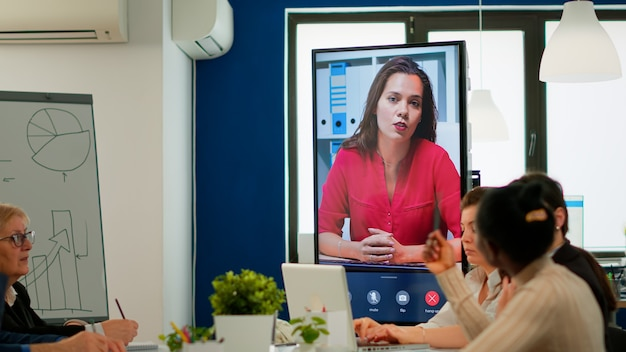 Multietchincal-team hört selbstbewusste geschäftsfrau webinar-sprecher trainer unternehmer lehrer reden blick in die kamera webcam video-trainings-vlog aufzeichnen, der online-geschäftskonferenzen macht