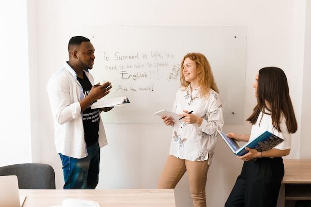 Multiethnisch glückliche schüler und schwarze lehrer lernen fremdsprachen und lächeln und lachen zusammen im unterricht