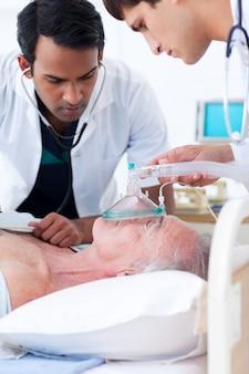Multiethnische ärzte, die einen älteren patienten wiederbeleben