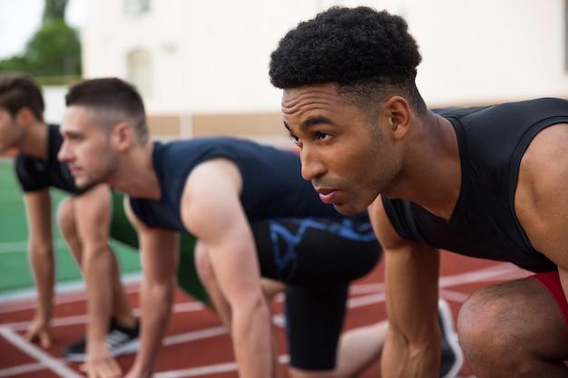 Multiethnische athletengruppe bereit zu laufen. konzentrieren sie sich auf den afrikanischen mann.