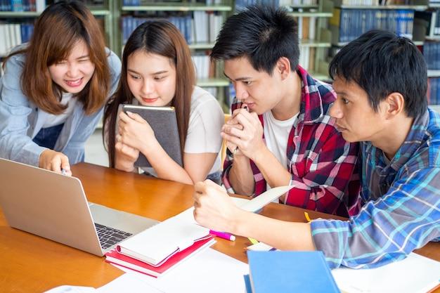 Multiethnische college-studenten, die testergebnisse überprüfen und laptop-bildschirm in bibliothek betrachten.