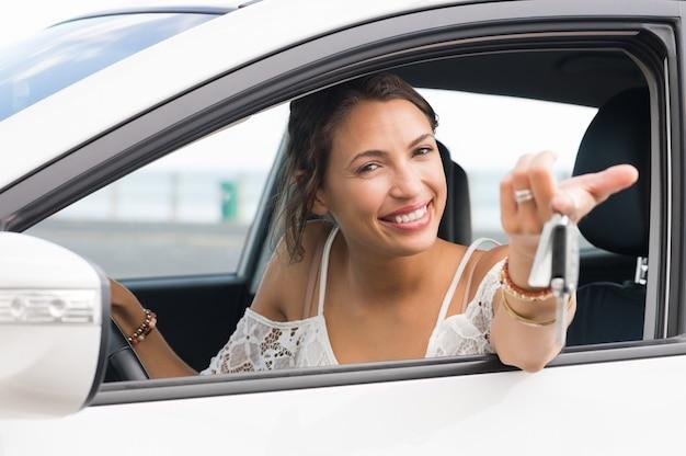 Multiethnische frau, die neue autoschlüssel und auto zeigt