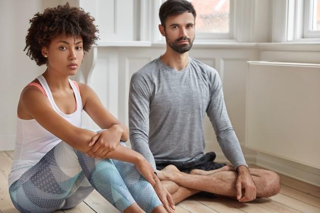 Multiethnische frau und mann meditieren gemeinsam auf dem boden, haben eine gute flexibilität, praktizieren yoga im häuslichen umfeld, schauen mit selbstbewusstem ausdruck, fühlen sich entspannt. menschen und konzentration
