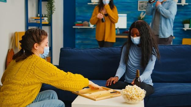 Multiethnische frauen, die backgammon spielen und eine gesichtsmaske tragen, um die ausbreitung von covid 19 während der globalen pandemie zu verhindern, sitzen auf dem sofa, trinken bier und essen popcorn. brettspiele im ausbruch genießen