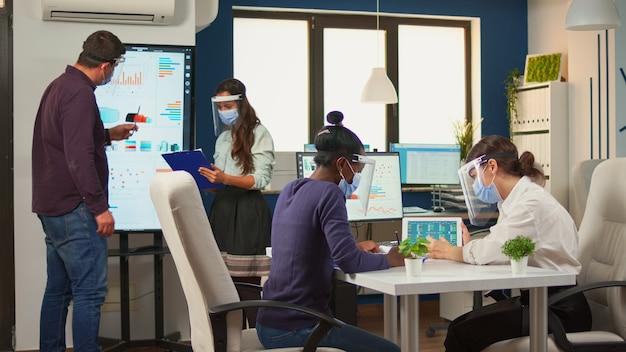 Multiethnische frauen mit schutzmasken, die jahresberichte analysieren diverse gruppe von geschäftsleuten, die im kreativbüro mit neuer normalität und unter wahrung der sozialen distanz zusammen arbeiten und kommunizieren.