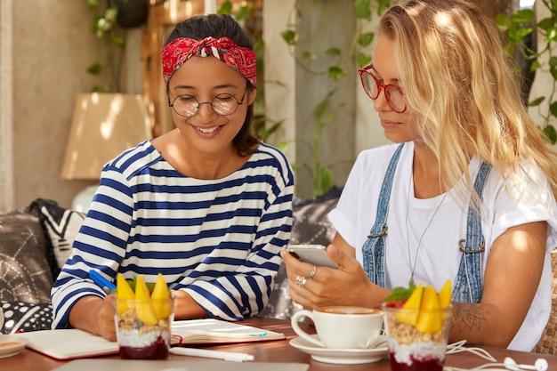 Multiethnische frauen verschiedener rassen, diskutieren die produktive strategie des designprojekts, schreiben einige ideen in ein notizbuch und sitzen mit dessert und kaffee im restaurant. asiatische journalistin nimmt interview